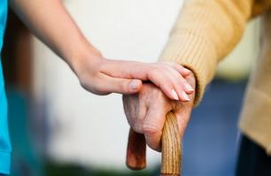 Mani di anziana e infermiera