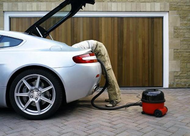 Uomo che pulisce il bagagliaio dell'auto
